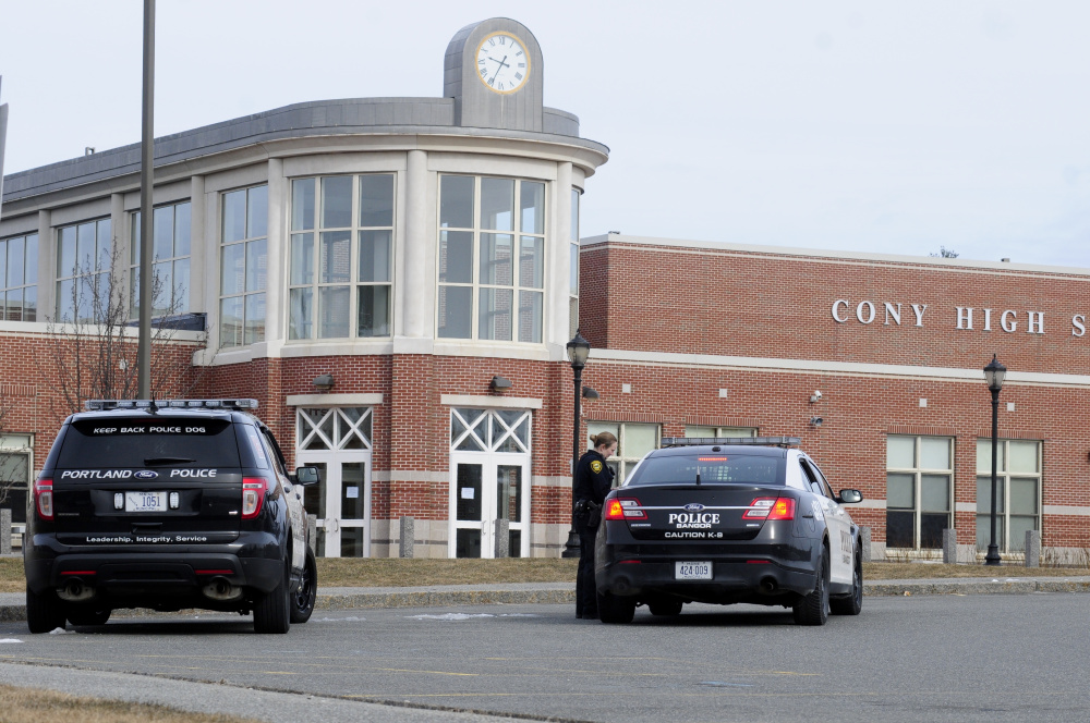 An Augusta police officer confers with officers from Bangor and Portland in front of Cony High School in Augusta after a bomb threat was emailed in to the school.
