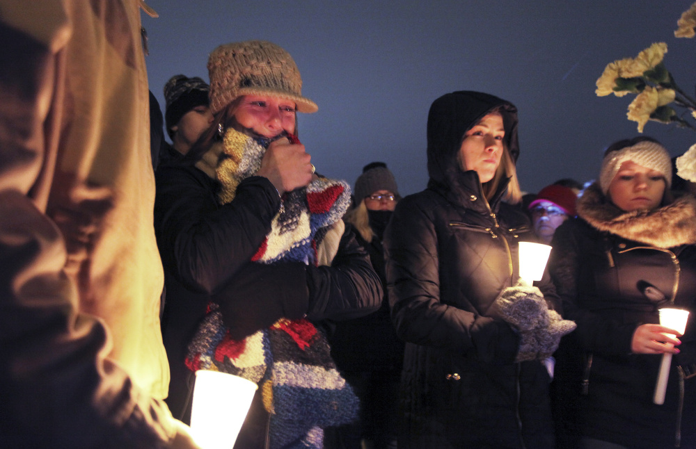 A woman hugs a prayer shawl as it gets passed through the crowd of more than 100 people at Friday night's vigil for missing Maine Maritime Academy student David Breunig.