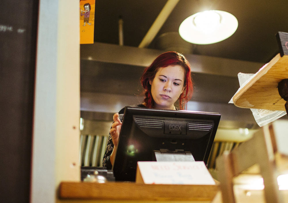"""Ambre Davidson works the register at Hilltop Superette in Portland. Davidson, a single mother who also works for a limousine service, says that a proposed $12-an-hour statewide minimum wage would have """"a huge impact"""" on her finances."""