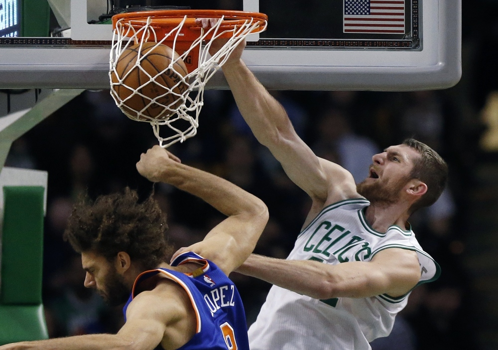 The Celtics' Tyler Zeller dunks over the Knicks' Robin Lopez in the dramatic fourth quarter of Friday night's game in Boston.
