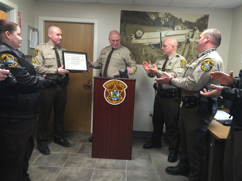Cpl. Matthew Brann receives the Meritorious Service Award for his part in helping save the life of a truck driver who was shocked by electrical wires in December while delivering grain in New Vineyard.