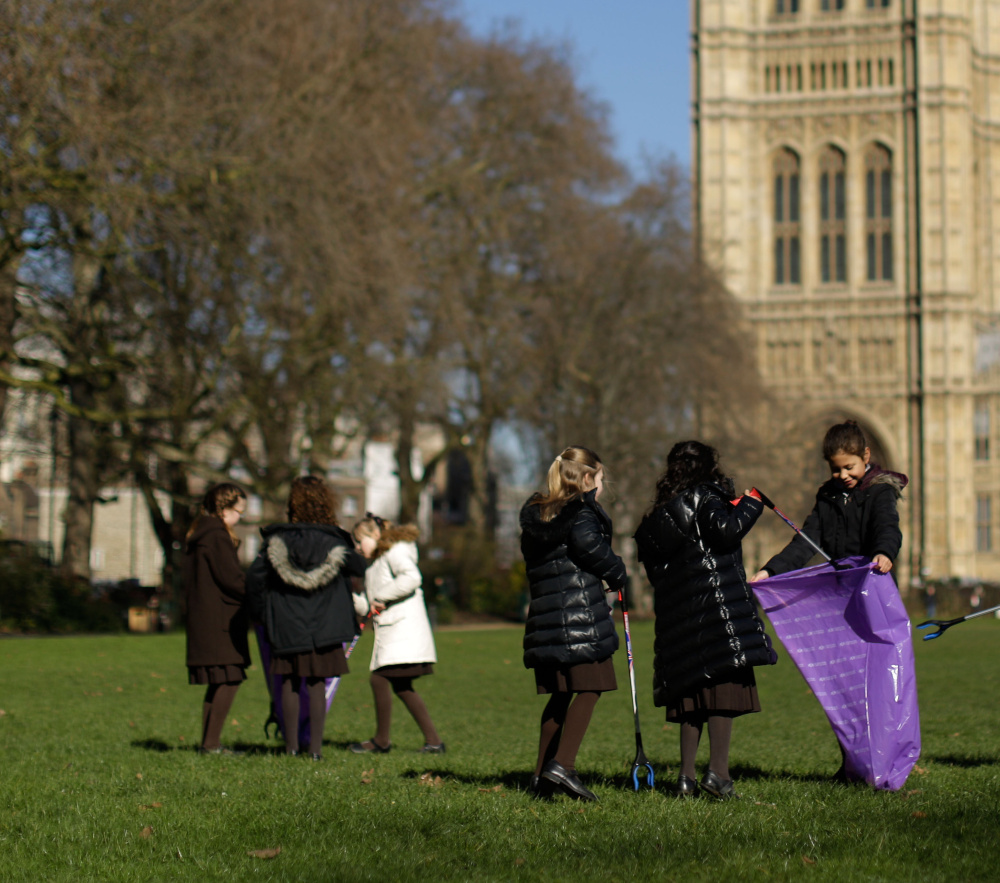 "Pupils from the Channing School for girls look for litter in Victoria Tower Gardens, next to the Houses of Parliament in London, during the ""Clean for the Queen"" campaign Friday."