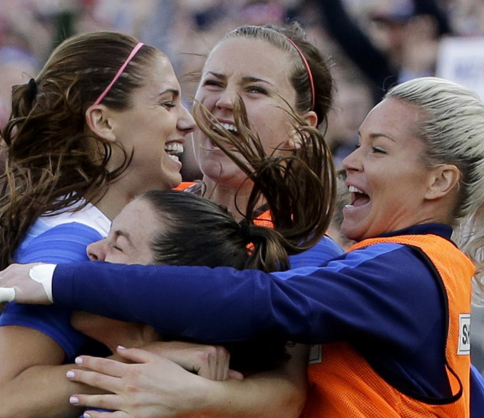 U.S. forward Alex Morgan, top left, celebrates with teammates after scoring the winning goal against France.