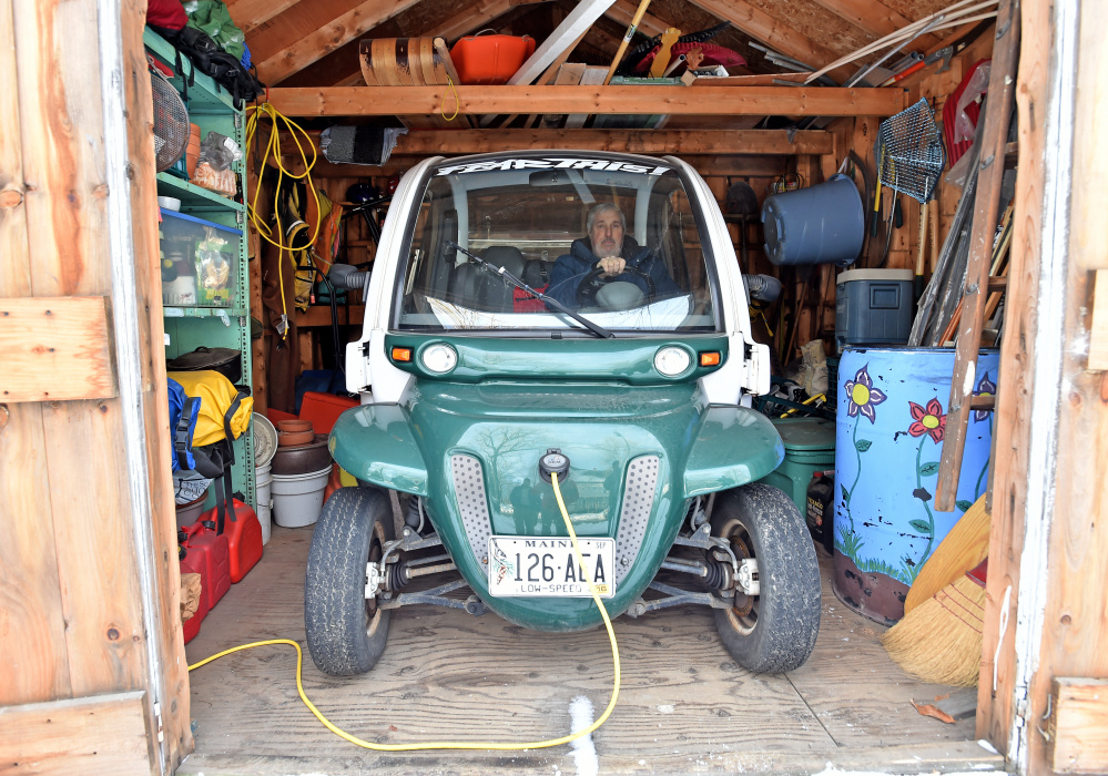 High school art teacher Iver Lofving sits in his electric car stowed in his shed at his home in Skowhegan.