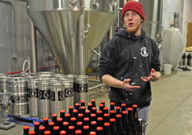 Standing in front of large stainless steel tanks, assistant brewer Michael Nugent talks about the brewing process at Lost Orchard Brewing Co.in South Gardiner. Joe Phelan/Kennebec Journal