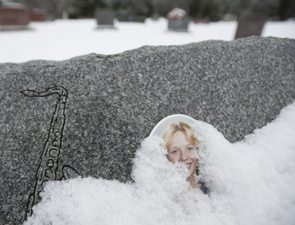 A portrait of Joyce McLain that is affixed to her gravestone peeks out from under snow in the cemetery Monday.
