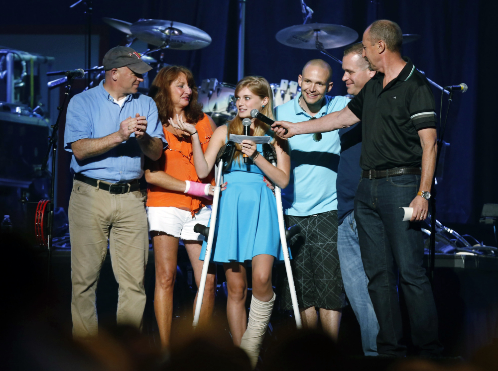 McGrath, center, thanks people who helped her after she was injured in the bombing, during the Boston Strong Concert: An Evening of Support and Celebration at the TD Garden in Boston.