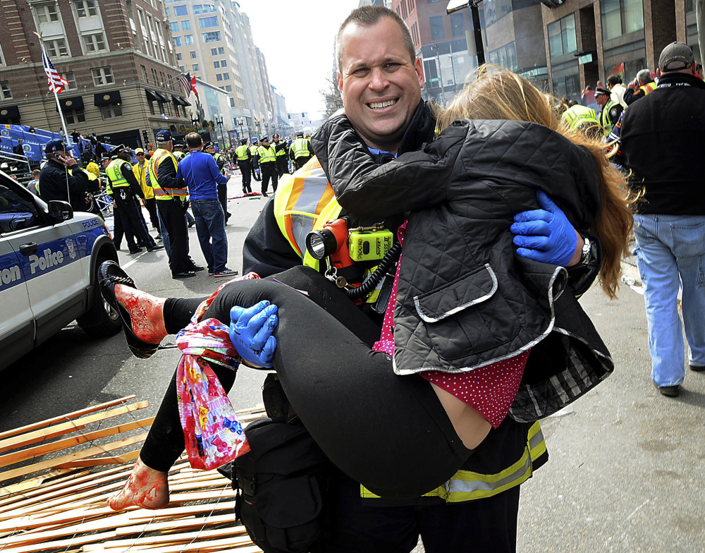Boston Firefighter James Plourde carries Victoria McGrath from the scene after a bombing near the Boston Marathon finish line in this April 15, 2013 file photo. McGrath, originally from Westport, Conn., and another student were killed in a car accident in Dubai over the weekend while on a personal trip.