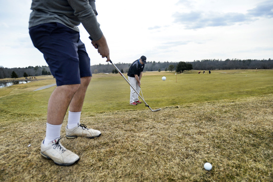 Mike Steinberg of Falmouth, in shorts, chips past golfing partner Jake Lachance of Falmouth onto the putting green at Nonesuch River Golf Club in Scarborough. More than 200 golfers played the course Wednesday, said General Manager Dan Hourihan.