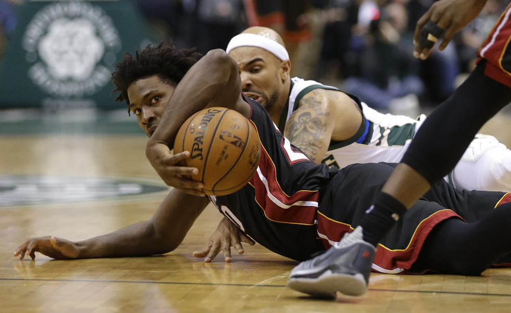 Justise Winslow of the Miami Heat, foreground, and Jerryd Bayless of the Milwaukee Bucks scramble for a loose ball Wednesday night during the first half of Milwaukee's 114-108 victory at home.