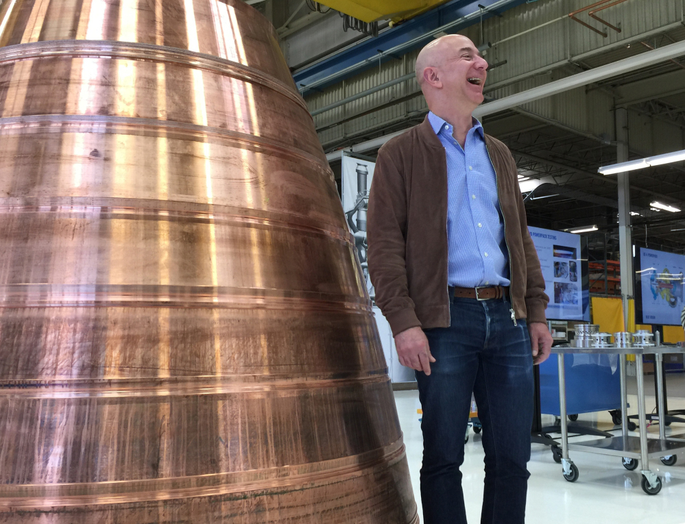 Amazon.com founder Jeff Bezos stands next to a copper exhaust nozzle to be used on a space ship engine, during tour of Blue Origin, in Kent, Wash. At left, Blue Origin team members ready the New Shepard Crew Capsule during assembly in Kent, Washington.