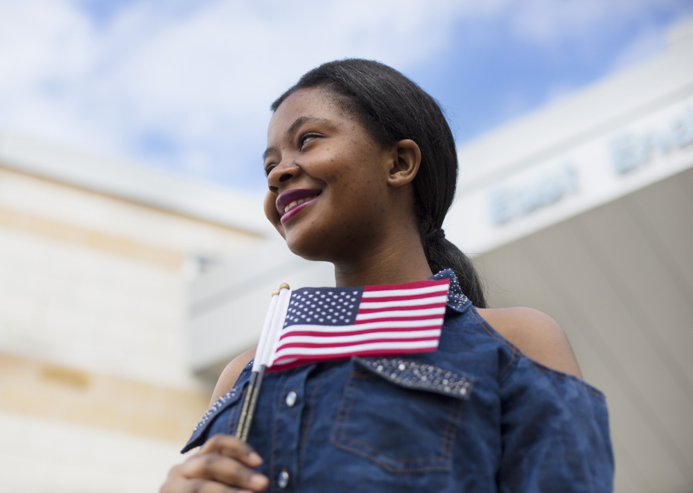 Mwange Mulonda, 19, of Lewiston, who is originally from the Democratic Republic of the Congo, poses for a portrait after the naturalization ceremony in Portland on Friday.