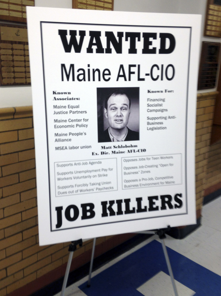 One of three wanted posters that drew criticism of Maine Gov. Paul LePage rests on a stand at the governor's town hall forum in Bath on Thursday. The posters, put up by LePage's staff, targeted the Natural Resources Council of Maine, Maine People's Alliance and Maine AFL-CIO.