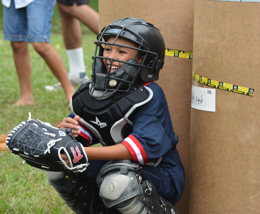 Many of the kids in Honduras were afraid to put on the equipment and catch, but this young boy was excited and had a great time – in front of a makeshift backstop of shipping barrels.