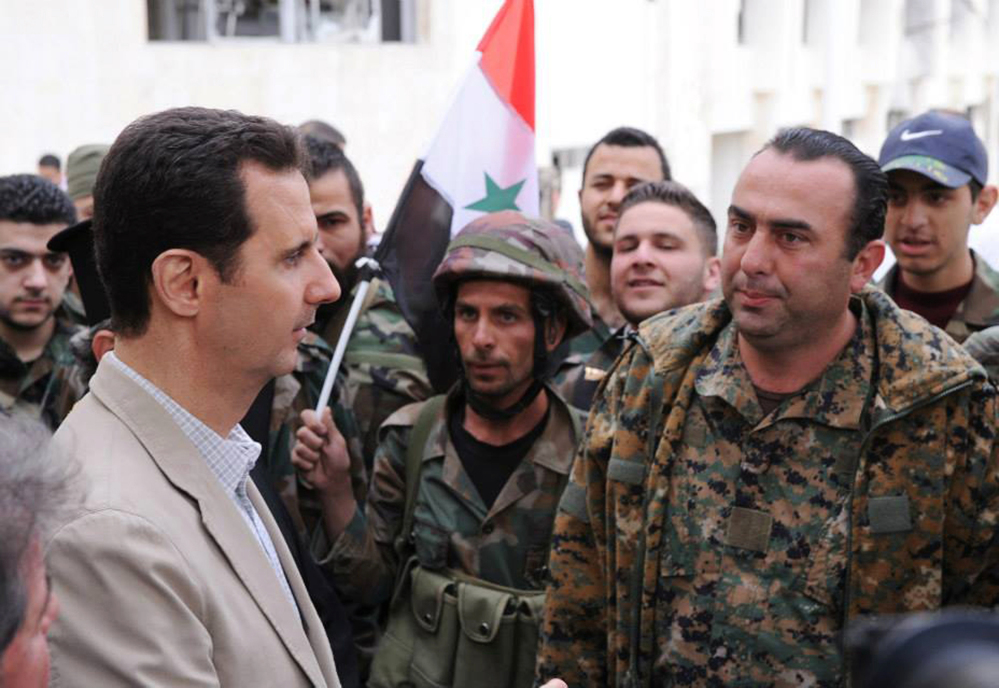 Syrian President Bashar Assad, left, talks to government soldiers during his visit to the Christian village of Maaloula, near Damascus, last April.
