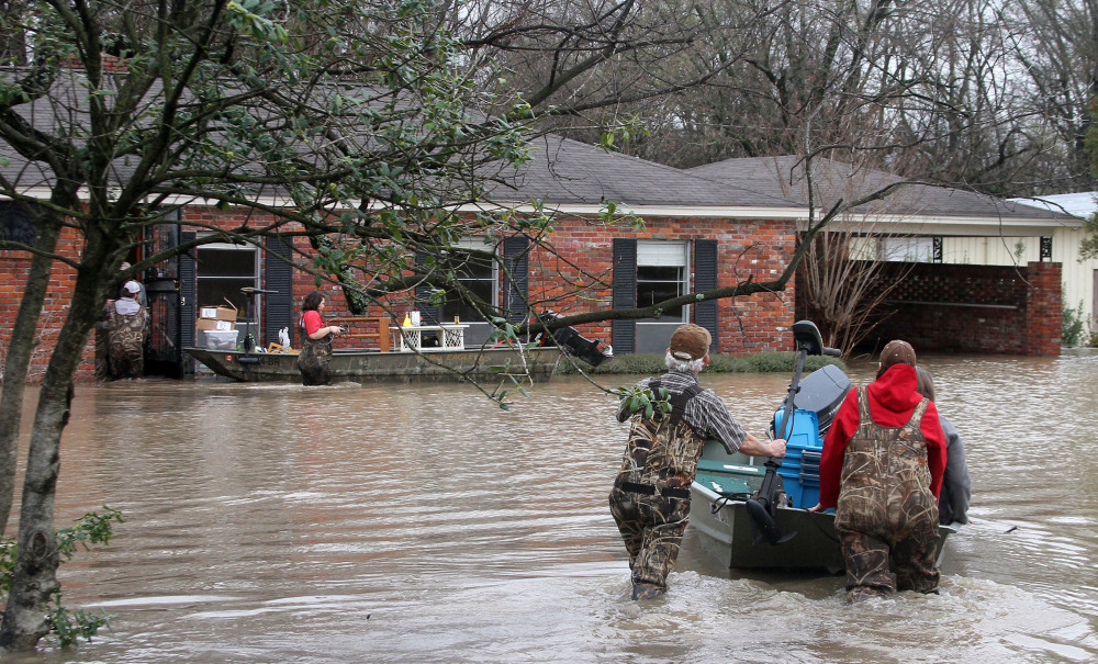 Volunteers return to a flooded house in Clarksdale, Miss., Friday, to assist the owners retrieve personal items as floodwaters continued to rise after another morning of rain.