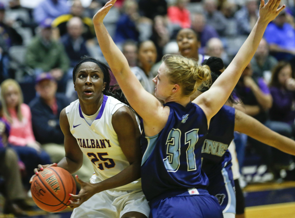 Albany forward Shereesha Richards drives on Maine forward Liz Wood during the second half Friday, in Albany, N.Y. Albany won 59-58. The Associated Press