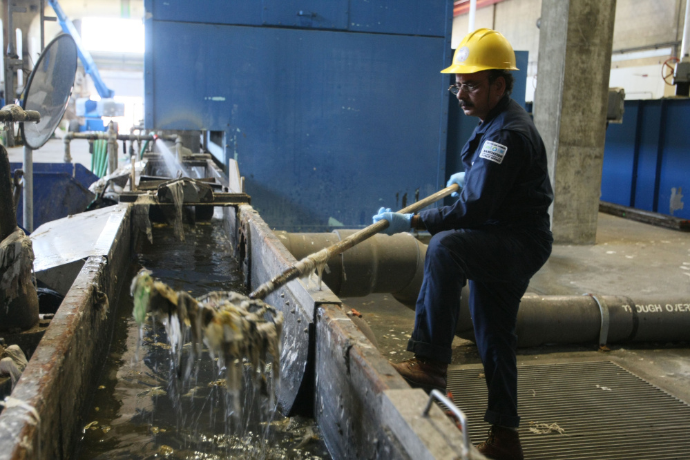 Ameen Uddin removes trash that has been separated from incoming wastewater at the Hyperion sewage treatment plant in 2012 in Los Angeles. Tribune News Service photo
