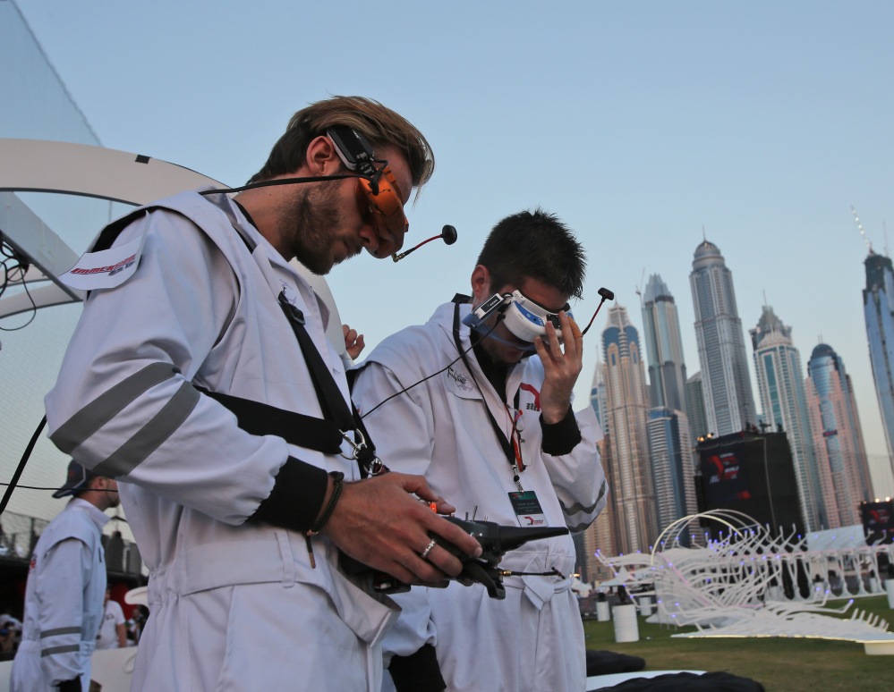 Fill Freybott, pilot of Freybott team of Germany, left, controls the team's drone during the first World Drone Prix in Dubai, United Arab Emirates, on Saturday.