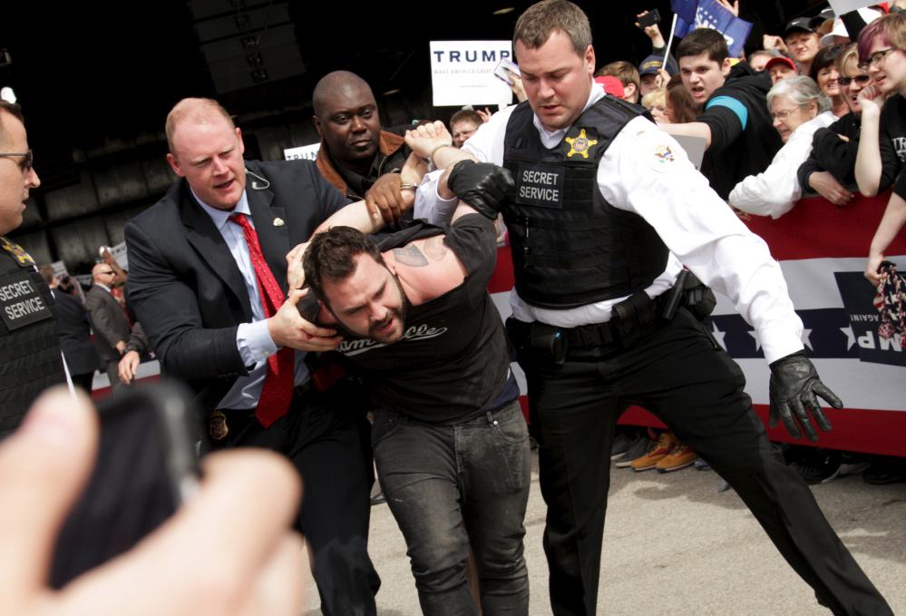 Secret Service agents detain a man after a disturbance at Donald Trump's rally Saturday in Dayton, Ohio, where he figures to outpoll popular Gov. John Kasich.