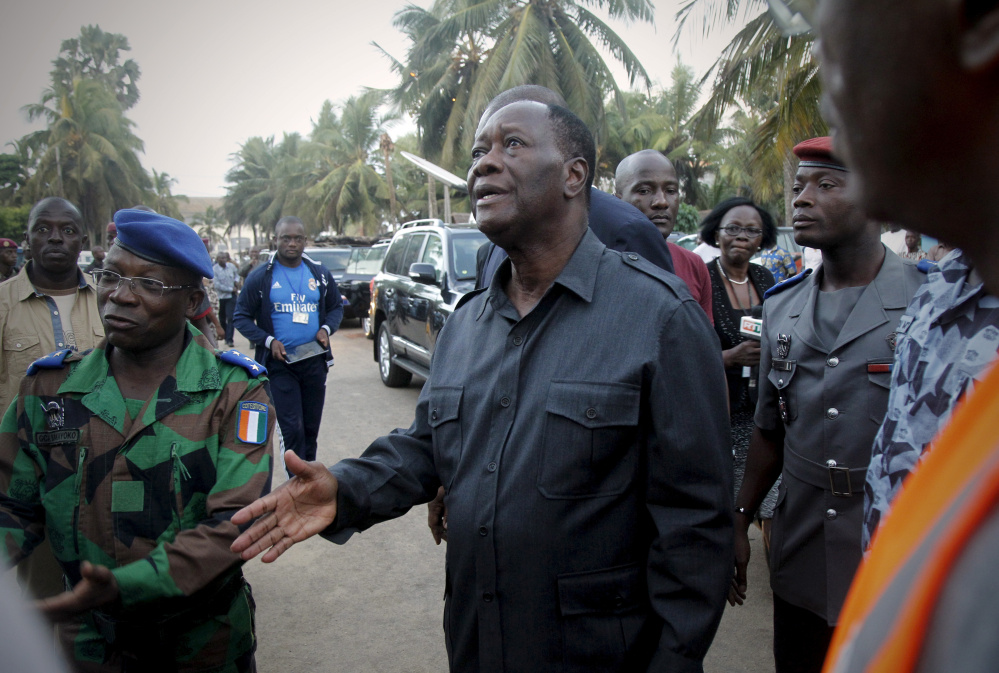 Ivory Coast President Alassane Ouattara, center, arrives at the hotel Etoile du Sud in Grand-Bassam a few hours after gunmen terrorized beachgoers on Sunday.