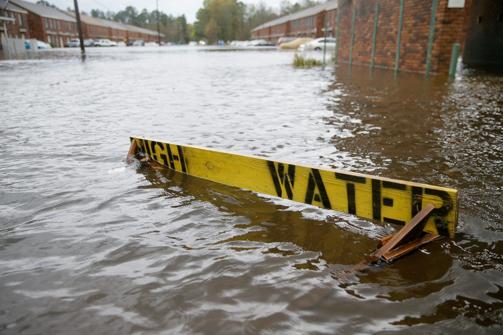 "Floodwaters partially submerge a ""high water"" sign on Rufus Bankston Road west of Hammond, La., on Friday."
