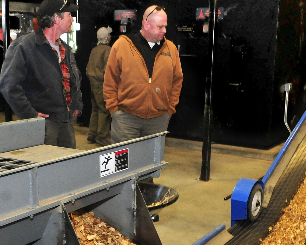 Doug Dubord, left, and Jon Baker watch as wood chips move on a conveyor into the biomass boiler at the University of Maine Farmington on Sunday.