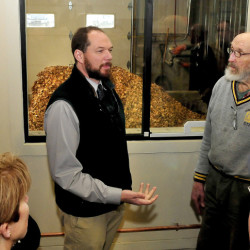 Outside a wood chip storage room, University of Maine Farmington Director of Facilities Jeff McKay, left, explains the process of using wood chips to produce energy to Tom Bissell and others on a tour of the UMF Central Heating Plant on Sunday.