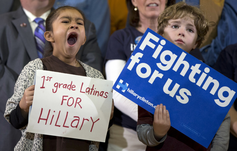 A little girl yawns as she holds her sign on stage behind Democratic presidential candidate Hillary Clinton during a campaign event at Chicago Journeymen Local Plumbers Union in Chicago on Monday. The Associated  Press