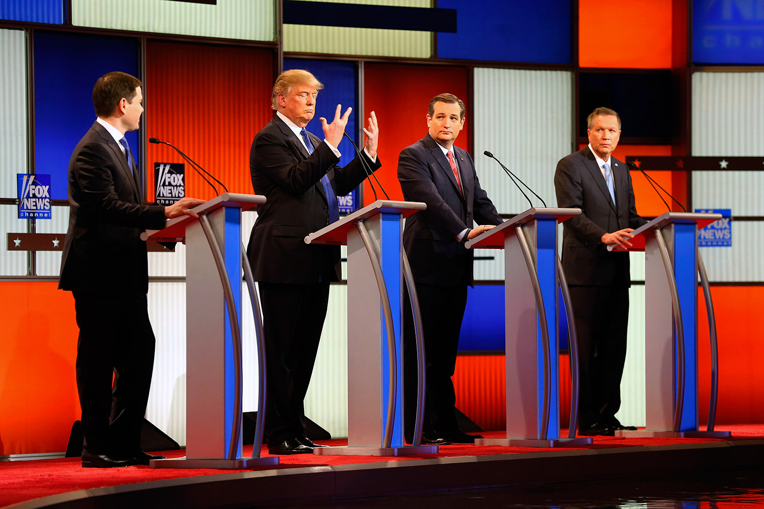 """Donald Trump shows his hands as Marco Rubio, Ted Cruz and John Kasich watch. Trump noted that Rubio had mocked his hands as small – widely viewed as an insult about Trump's sexual prowess – and said, """"I guarantee you, there's no problem"""" in that area. The Associated Press"""