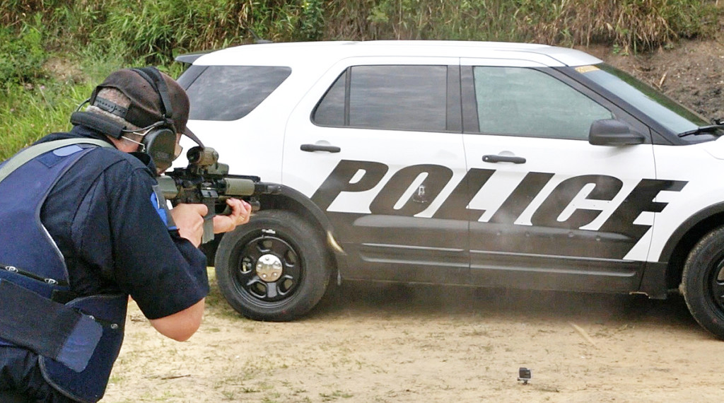 A Michigan State Police officer shoots at the doors of a Ford Police Interceptor Utility vehicle during ballistic testing of doors that meet the Justice Department's highest standard for body armor, the equivalent of a bulky SWAT team vest. Ryan Koehler/Ford Motor Company via AP
