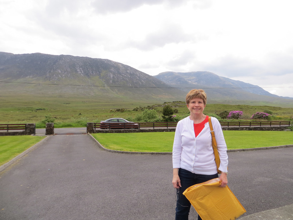 Deb Sullivan Gellerson of Gray, DNA genealogy results in hand, stands in May 2014 in the driveway to the home of her third cousin Kevin Coyne, a Joyce family member who lives near the Maamturk Mountains in Maam, County Galway, Ireland.
