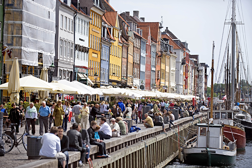 Visitors crowd Nyhan, a 17th-century canal and entertainment district in Copenhagen. In a study of 156 countries, the U.N. has determined Danes to be the happiest people on Earth. The Associated Press