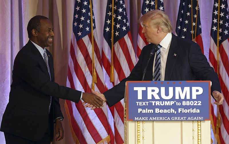 Former Republican presidential candidate Ben Carson and Donald Trump shake hands on March 11, 2016, after Carson announced he would endorse Trump for president.