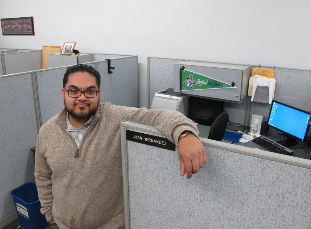Juan Hernandez poses at his work cubicle in Hartford City Hall. Hernandez, 25, is among millennials nationwide with student debt who are worried about being able to qualify for a loan and come up with a down payment for a home.    The Associated Press