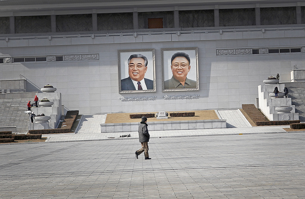 A man walks past portraits of the late North Korean leaders Kim Il Sung and Kim Jong Il, at the Kim Il Sung Square on Feb. 14, 2016, in Pyongyang. North Korea launched a rocket Feb. 7, carrying what it said was an Earth observation satellite into space. World leaders called it a  banned test of ballistic missile technology and another