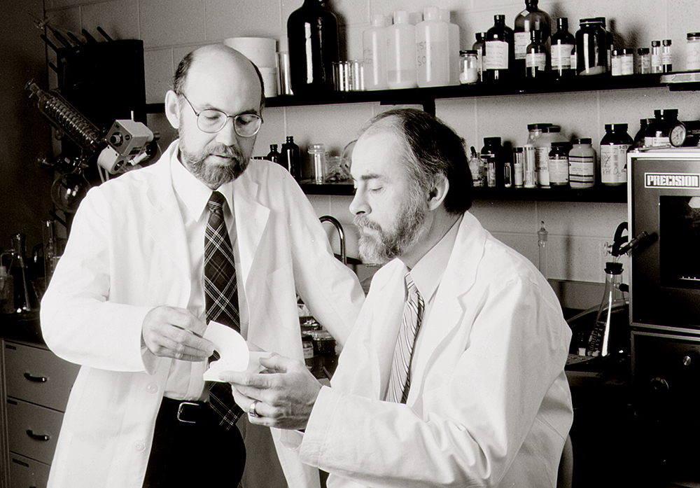 Spencer Silver, left, and Art Fry hold a Post-It Note pad. 3M says Fry and Silver developed the iconic product