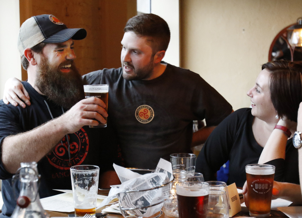Andy Geaghan of Geaghan Brothers Brewing, left, Chris Bougie and Lisa Sturgeon raise a glass at the Little Tap House after the summit Friday.