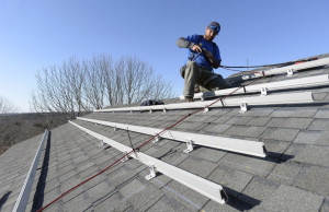 Zach Good of ReVision Energy prepares a roof for solar panels at a private home in Cape Elizabeth in 2015.