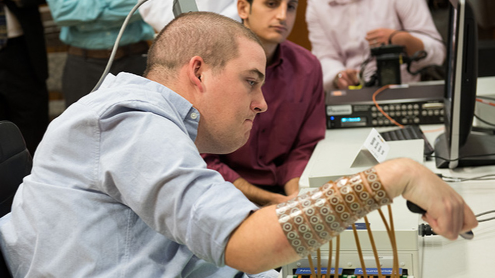 Ian Burkhart participates in a study with neural bypass technology at The Ohio State University Wexner Medical Center in Columbus. A computer chip in Burkhart's brain reads his thoughts, decodes them, then sends signals to a sleeve on his arm that allows him to move his hand.