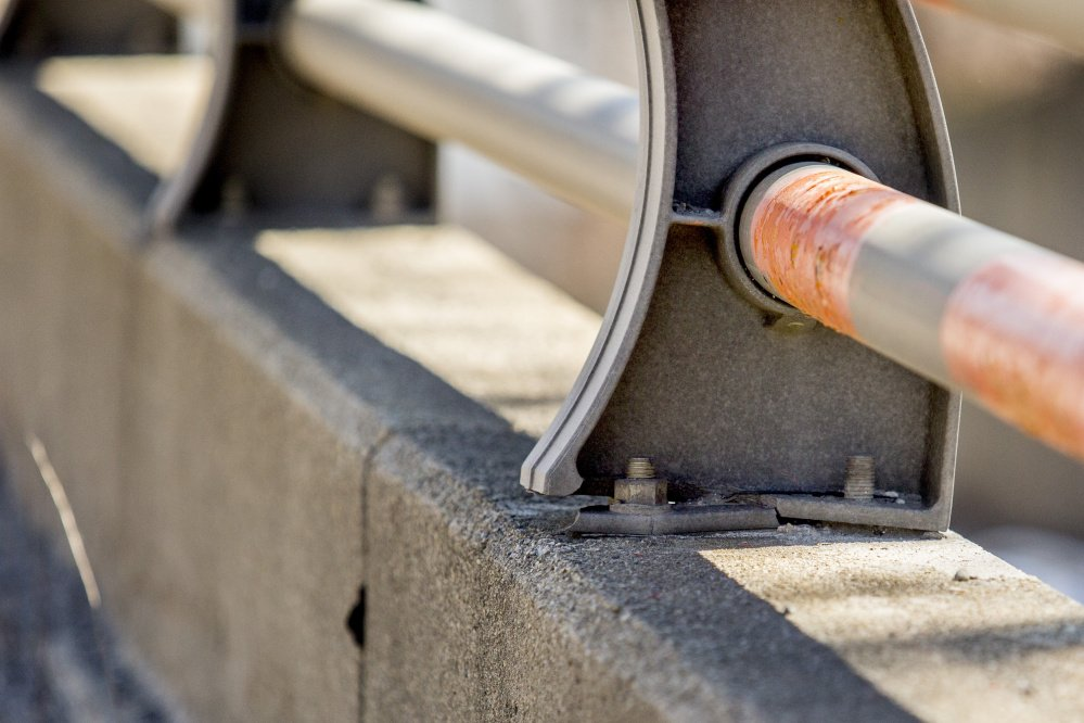 A guardrail support post is cracked and a nut is missing from the bolt at right on the Bath Viaduct. A 2014 inspection by a private contractor suggested that the Maine DOT repair the viaduct railing in six places.