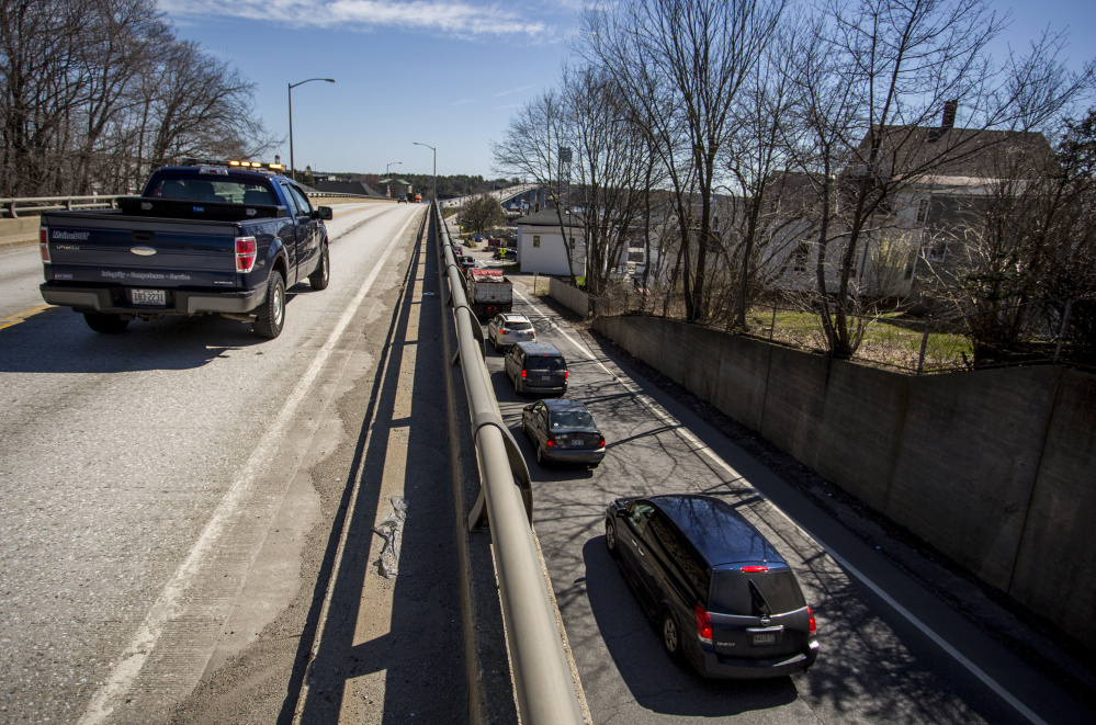 A Maine Department of Transportation truck sits on the Route 1 viaduct in Bath during a bridge inspection as traffic packs Commercial Street below.