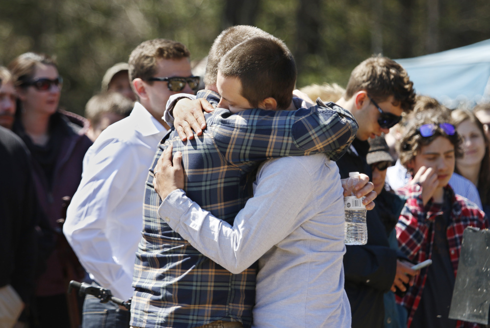 Friends of Adam Perron embrace at the memorial service.