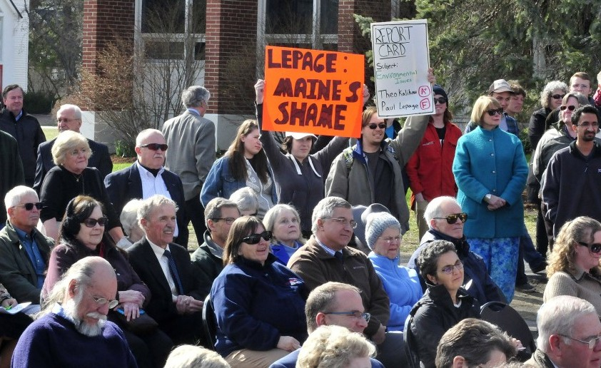 University of Maine at Farmington students Allyson Hammond, left, and Nickolas Bray hold up posters critical of Gov. Paul LePage during the dedication of the Theodora J. Kalikow Education Center at the campus on Tuesday.