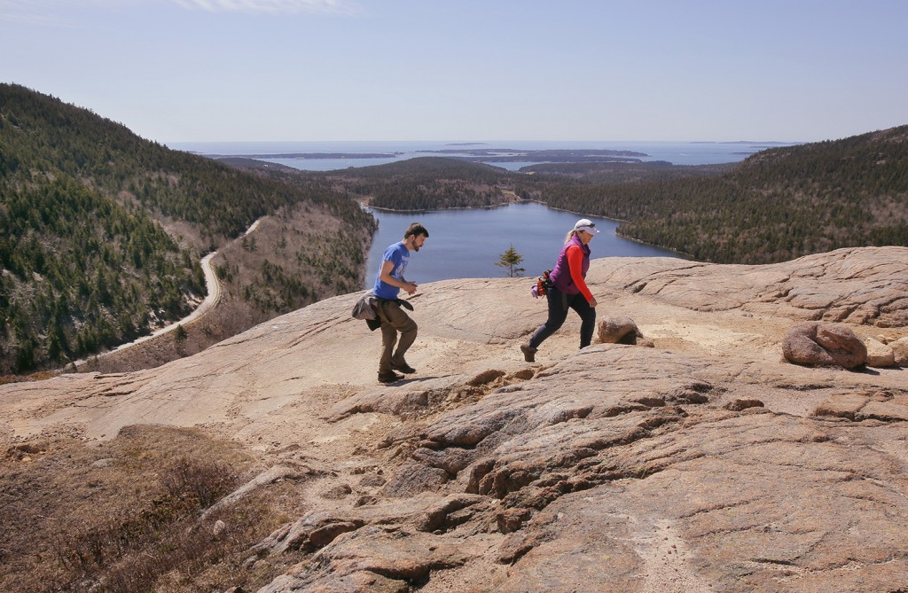 Ryan Reynolds of Hacock, left, and Florence Dunbar of Southwest Harbor hike over the summit of South Bubble in Acadia National Park on April 30. Gregory Rec/Staff Photographer