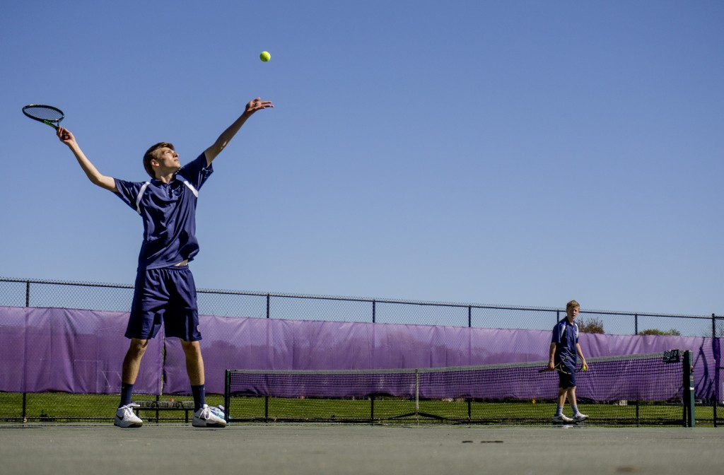 Peter Barry, a junior at Portland, tosses up a ball to serve to Isaac Finberg of Deering during a tennis match at Deering Wednesday. Gabe Souza/Staff Photographer