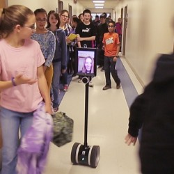 "This photo from video shows the robot nicknamed ""Double"" with Abby Fisher's image in a hallway at the Vassalboro Community School."
