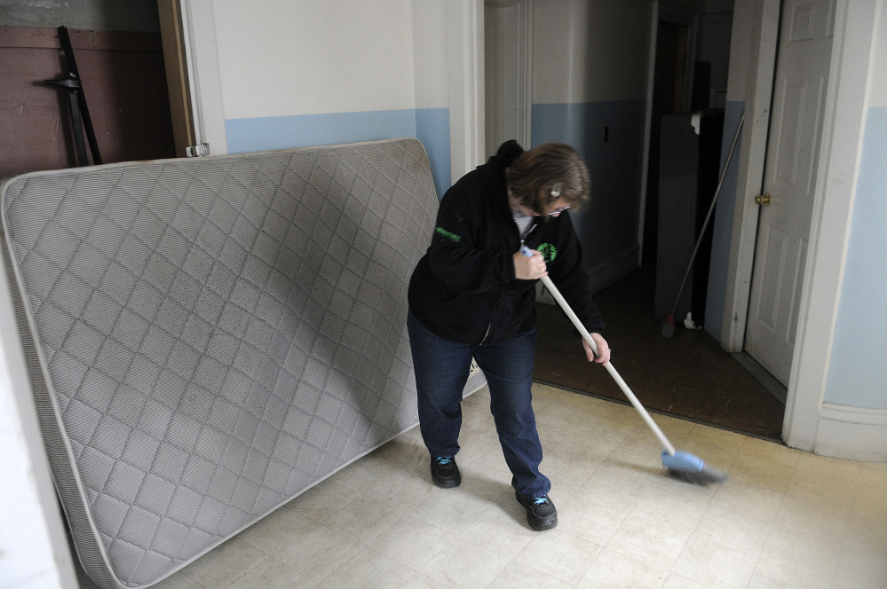 Andrea Anderson cleans the kitchenette and bathroom area Tuesday at 382 Water St. in Augusta.