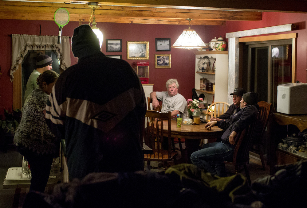 Carter McBreairty, center, listens to the conversation of friends and family around the dinner table of his home in Allagash, an Aroostook County town consisting of a dispersed collection of homes, hunting lodges and small businesses. Allagash is surrounded by industrial forests that stretch to the borders of Quebec, Canada, and Baxter State Park, 60 miles south.