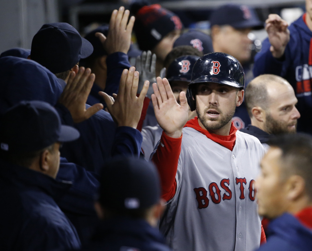 Boston Red Sox's Travis Shaw celebrates in the dugout after scoring on a sacrifice fly by Brock Holt during the third inning of a baseball game against the Chicago White Sox on Thursday, in Chicago.